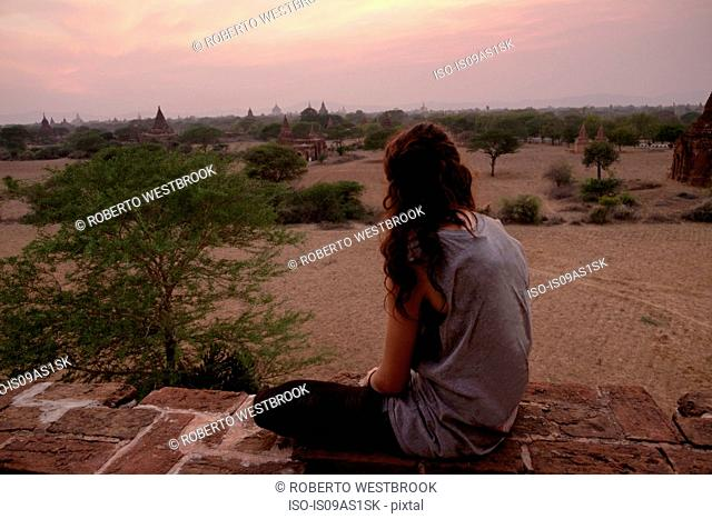 Woman looking at view from stone wall, Bagan Archaeological Zone, Buddhist temples, Mandalay, Myanmar