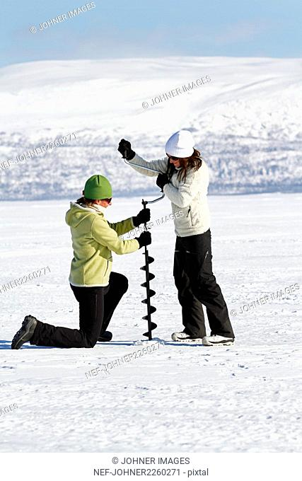 Women drilling hole in ice