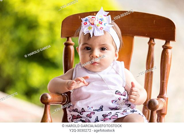 close up of a baby girl in a rocking chair