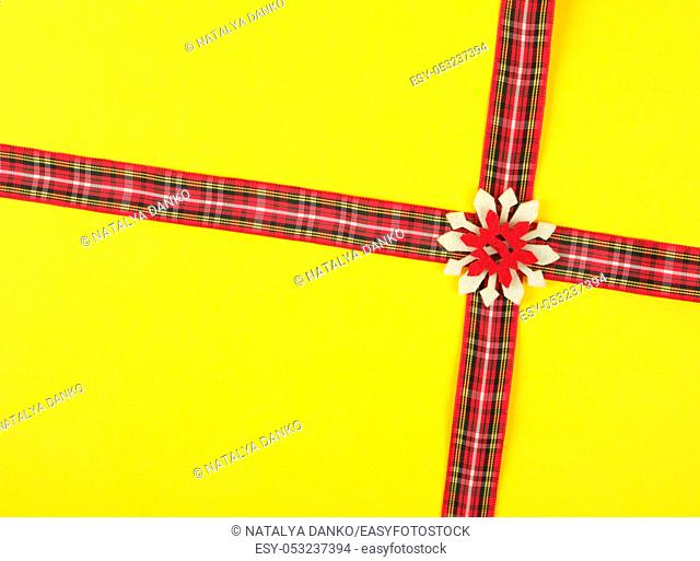 red decorative ribbon in a box cross on a cross on a yellow background, festive background
