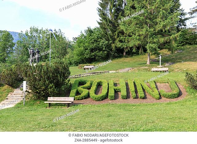 Statue of the four men in the center of Bohinj, with Bohinj text on foreground Slovenia