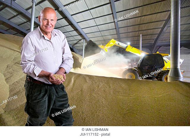 Portrait Of Farmer Inspecting Wheat Crop In Grain Store