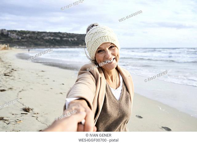 Spain, Menorca, portrait of happy senior woman holding hand on the beach in winter