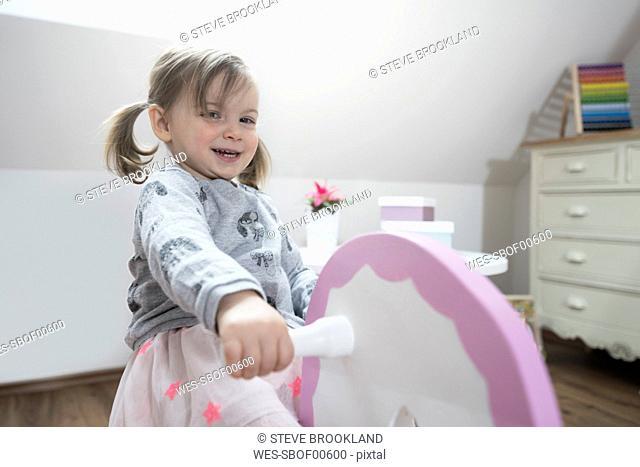 Happy toddler girl rocking on rocking horse in nursery