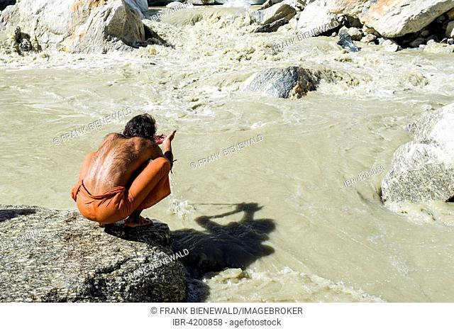 A Sadhu, holy man, is sitting and praying on a rock at Gaumukh, the main source of the holy river Ganges, Gangotri, Uttarakhand, India