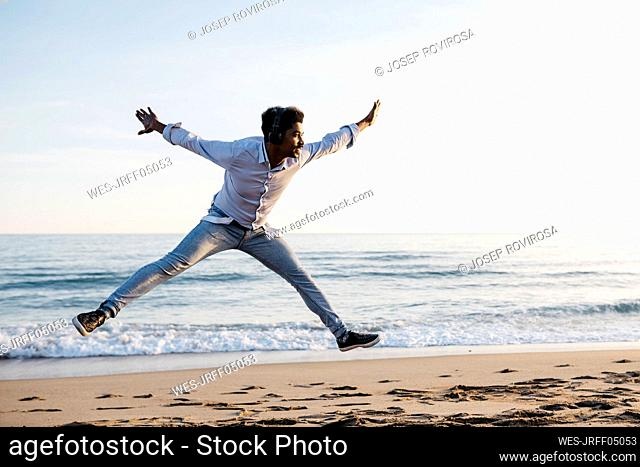 Cheerful man with arms outstretched jumping at beach against clear sky