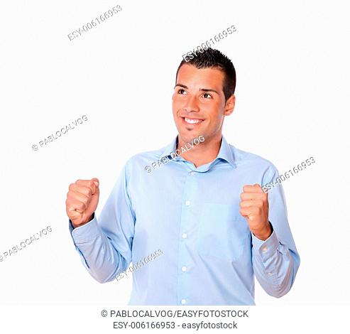 Portrait of a handsome young male on blue shirt celebrating his victory while smiling and looking at people on isolated background - copyspace