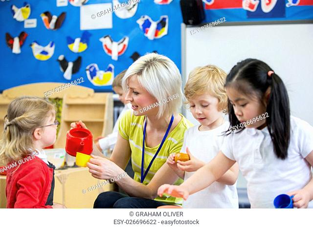 Nursery teacher playing kitchen roleplay with her students in the classroom. she is pouring a pretend cup of tea for a little girl