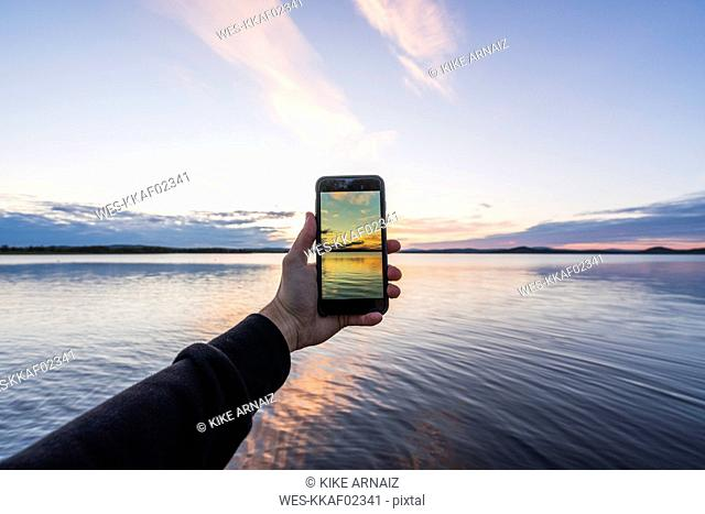 Finland, Lapland, man taking cell phone picture of stunning lake at twilight