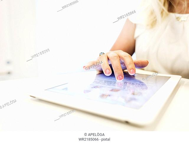 Cropped image of businesswoman using digital tablet in office