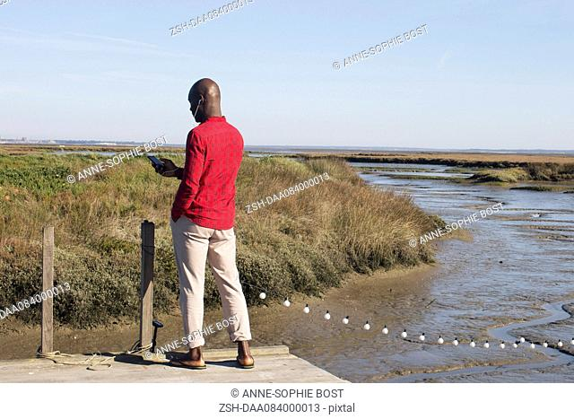 Man standing on dock, listening to music with earphones