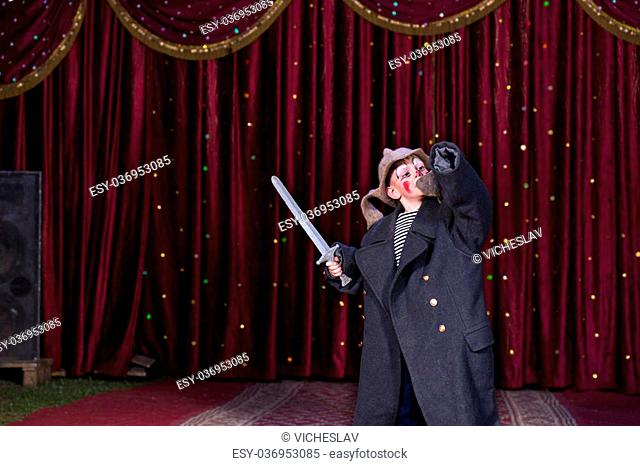 Young Boy Wearing Clown Make Up and Over Sized Coat Holding Toy Prop Sword with Arm Raised Standing on Stage with Red Curtain