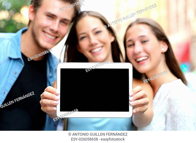 Three happy friends showing a blank tablet screen in the street