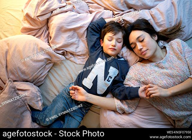 Mother and little son relaxing together on bed