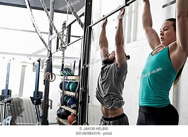 Couple doing chin-up in cross training gym