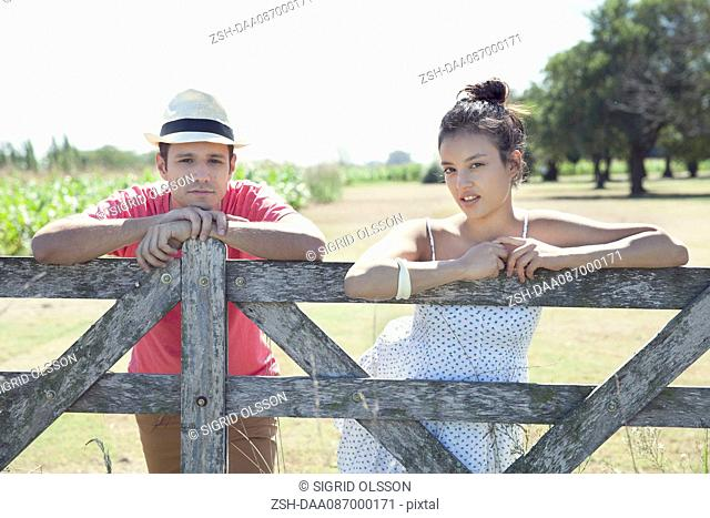 Couple learning against wooden fence, portrait