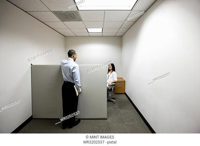 A black businessman talking to an Asian businesswoman working in a small corner cubicle office