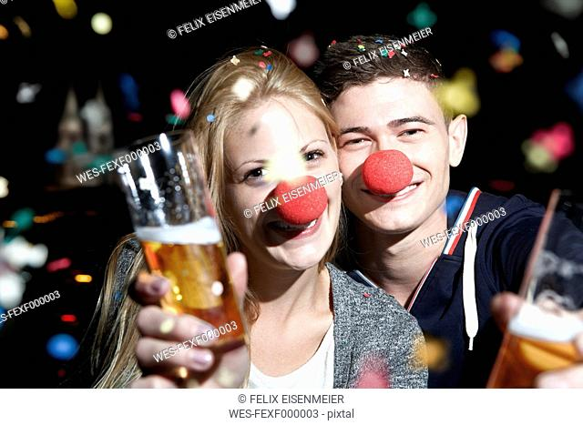 Germany, North Rhine Westphalia, Cologne, young couple with clowns noses toasting