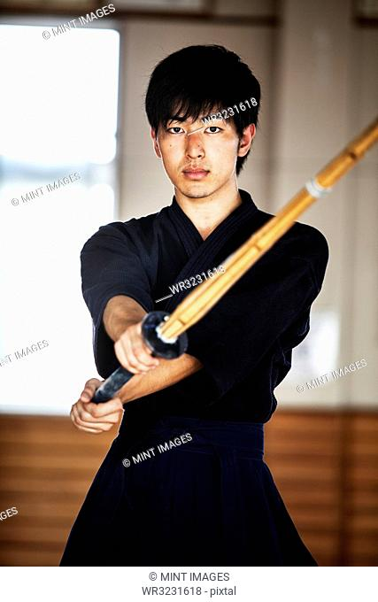 Male Japanese Kendo fighter holding wood sword in combat pose, looking at camera