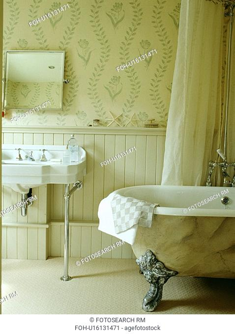Paint effect marbled clawfoot bath in cream bathroom with wallpaper and panelling to dado height