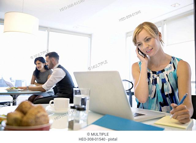 Businesswoman talking on cell phone working at laptop in office cafeteria