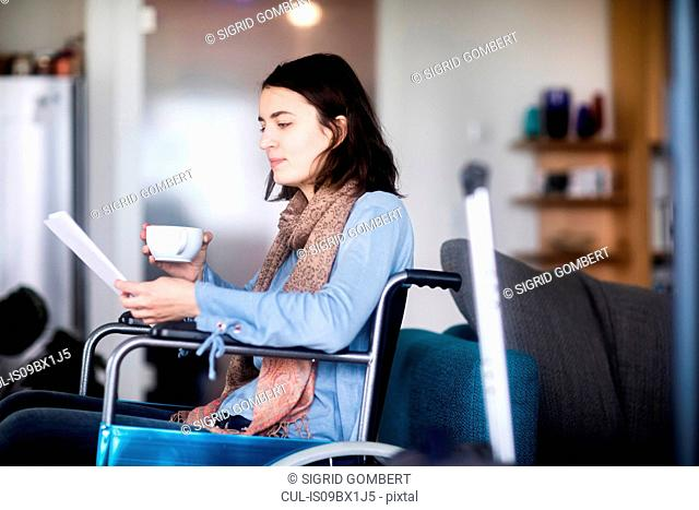 Woman in wheelchair reading at home