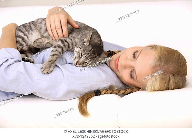 young blond woman fondling domestic cat