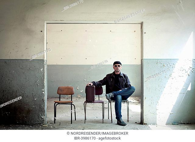 A traveller with a suitcase is sitting in an old building
