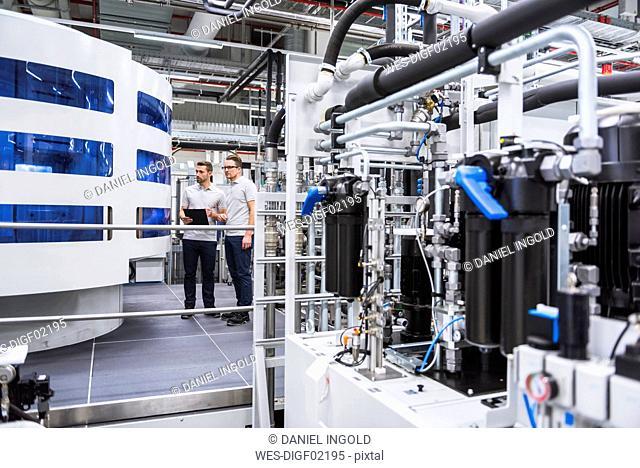 Two men looking at machine in factory shop floor