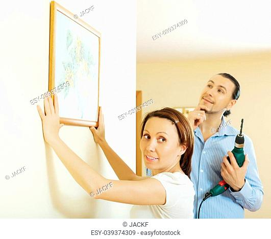 Middle-aged couple choosing point for picture on wall at home