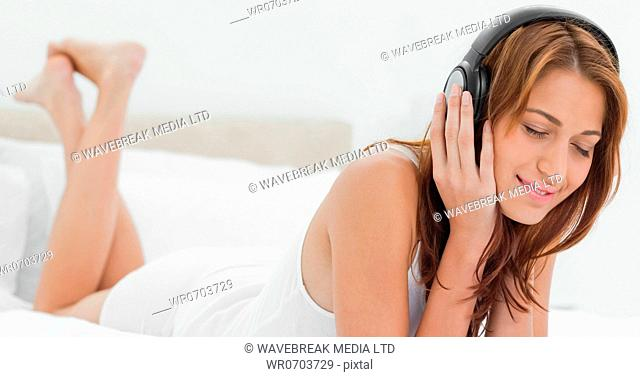 Close-up of a redhead woman enjoying music while lying on her belly in her bedroom