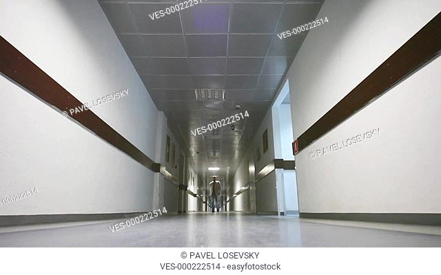Businessman comes through long corridor in office at camera, part2