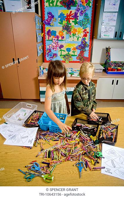 Kindergarten children in San Clemente, CA, collect and organize a table full of classroom objects including crayons and worksheets