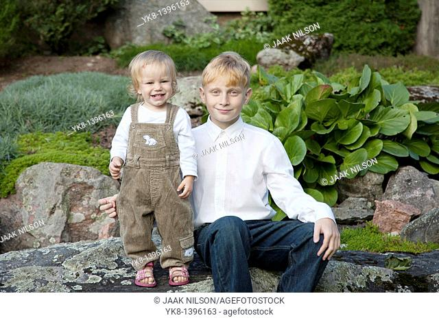 Happy Young Teenage Caucasian Boy with Kid Sister on Stone in Garden