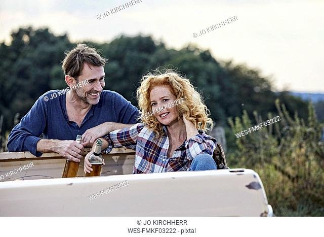 Couple at pick up truck having a beer