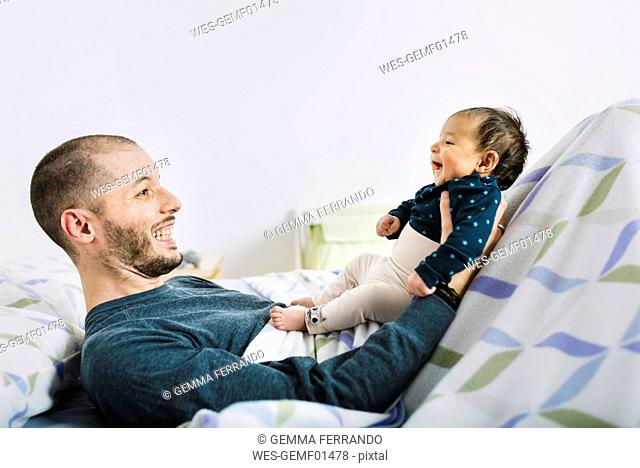 Happy father lying playing with his newborn baby girl in bed