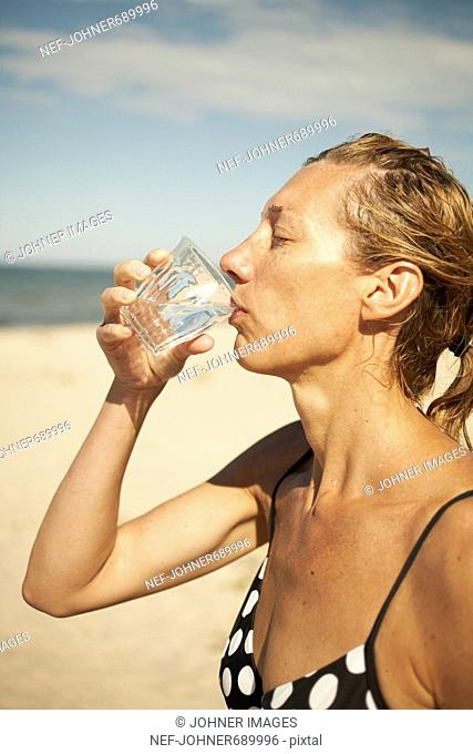 Woman having a glass of water on the beach, Sweden