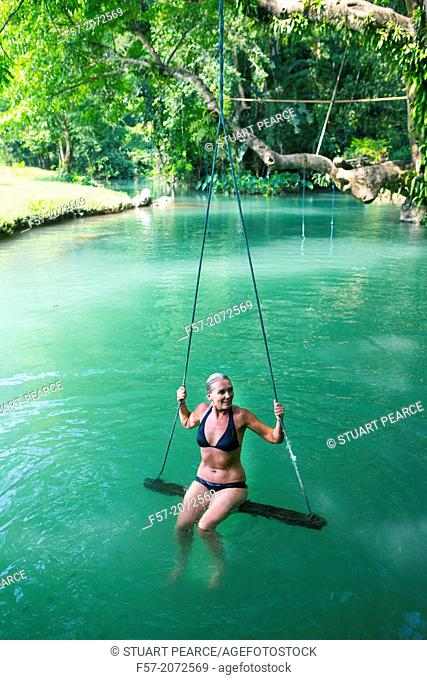Woman on a swing in the Blue Lagoon in Vang Vieng, Laos
