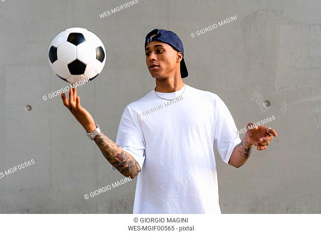 Portrait of tattooed young man balancing football on his finger in front of concrete wall