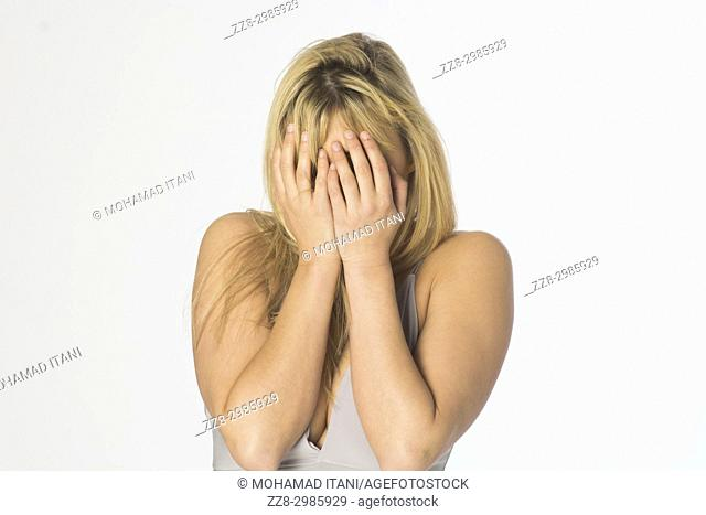 Young blond woman hiding face with hands against a white background