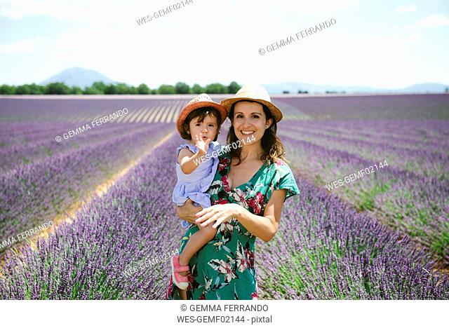France, Provence, Valensole plateau, portrait of smiling mother and daughter in lavender fields in the summer