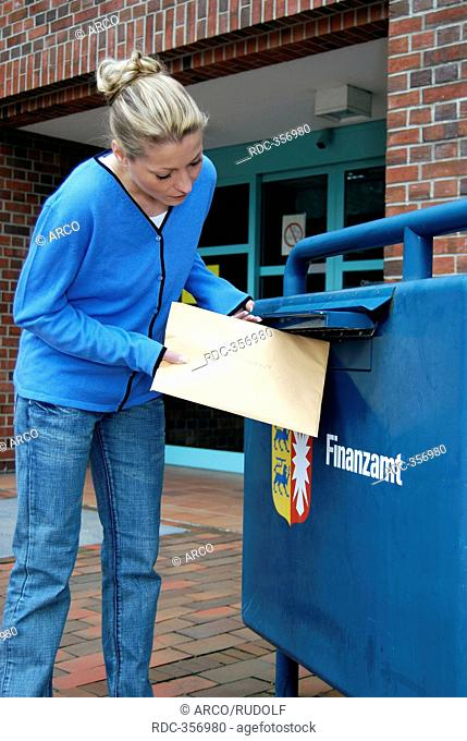 Youn woman posting letter, into mailbox, postbox, finance authority, taxman, filing her tax declaration, tax filing