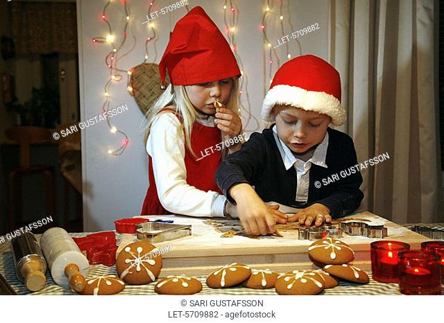 A boy and a girl bake ginger biscuits for Christmas