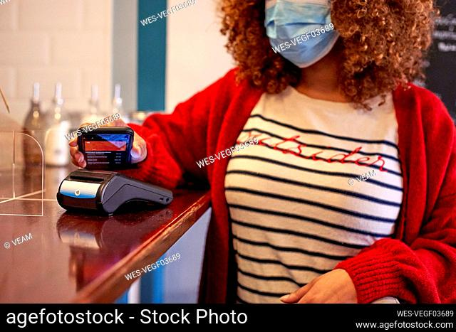 Afro woman wearing sanitary mask while making contactless payment through mobile phone at cafe