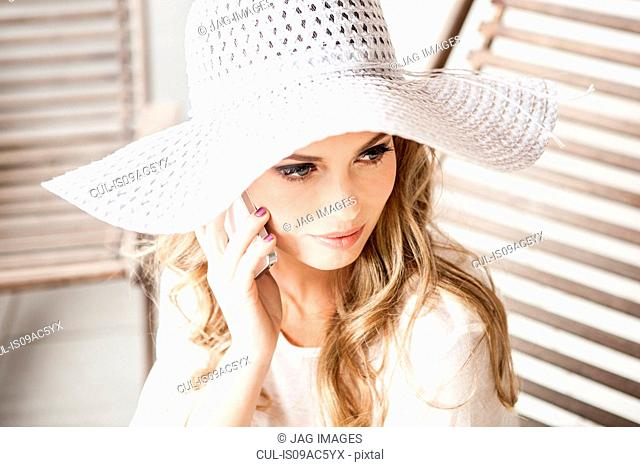 Glamorous young woman in sun hat, using cellphone
