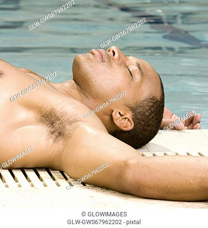 Close-up of a young man lying down at the poolside