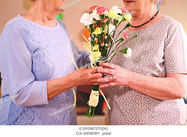 Senior woman giving flowers to friend at birthday party