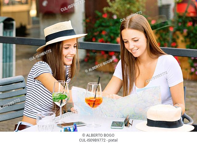 Two young female friends looking at map at sidewalk cafe