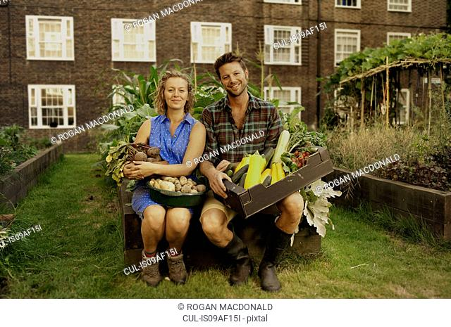Couple holding harvested vegetables on council estate allotment