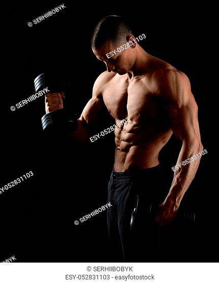 Workout for arms. Portrait of a young bodybuilder lifting weights at the studio on black background